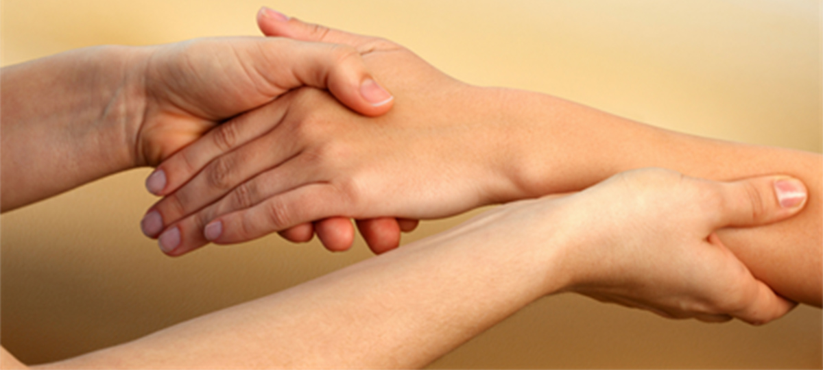 closeup of hands massaging a person's arm