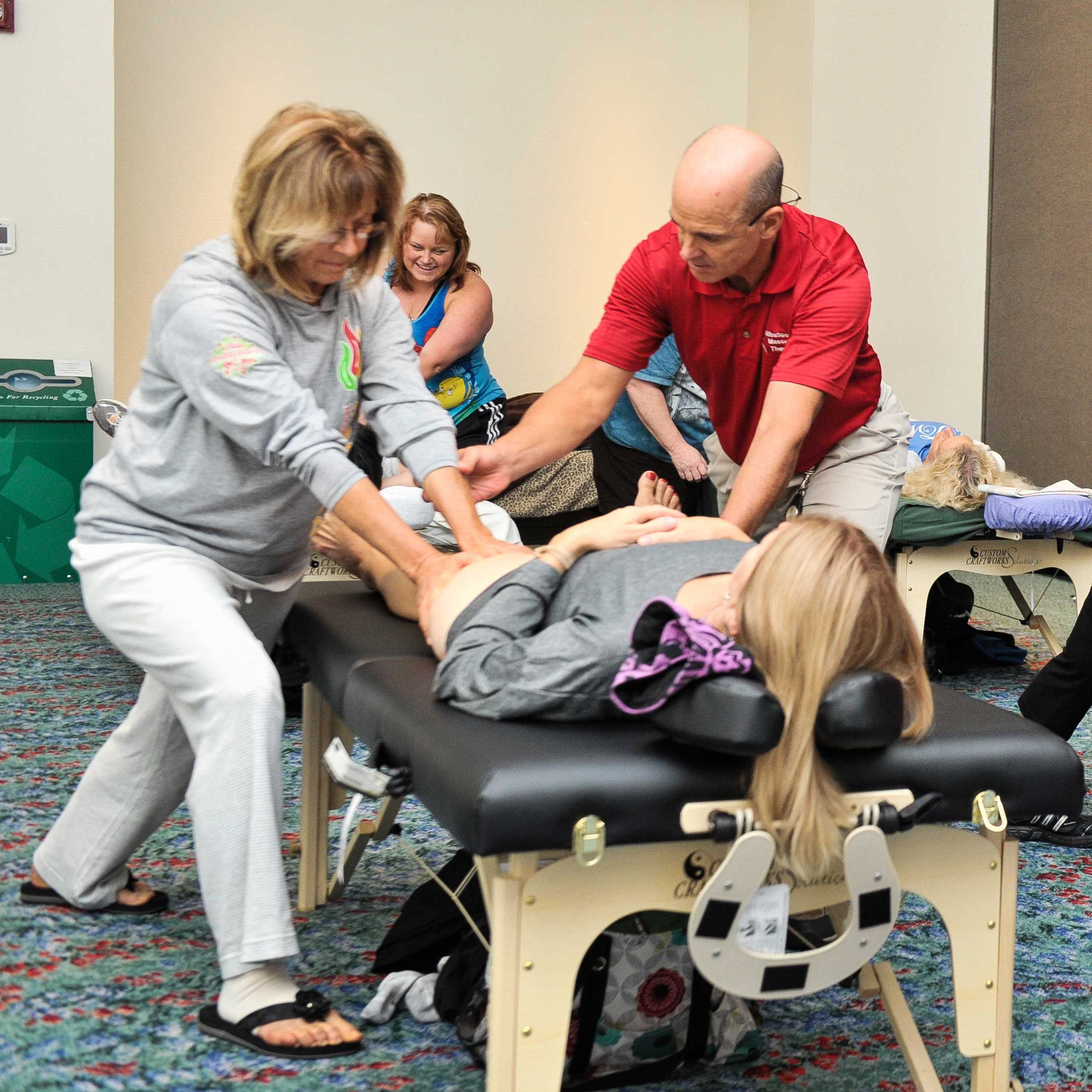 Massage teacher showing student a massage technique