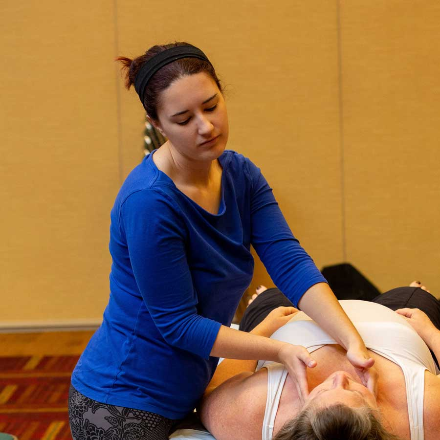 female massage therapist massaging client