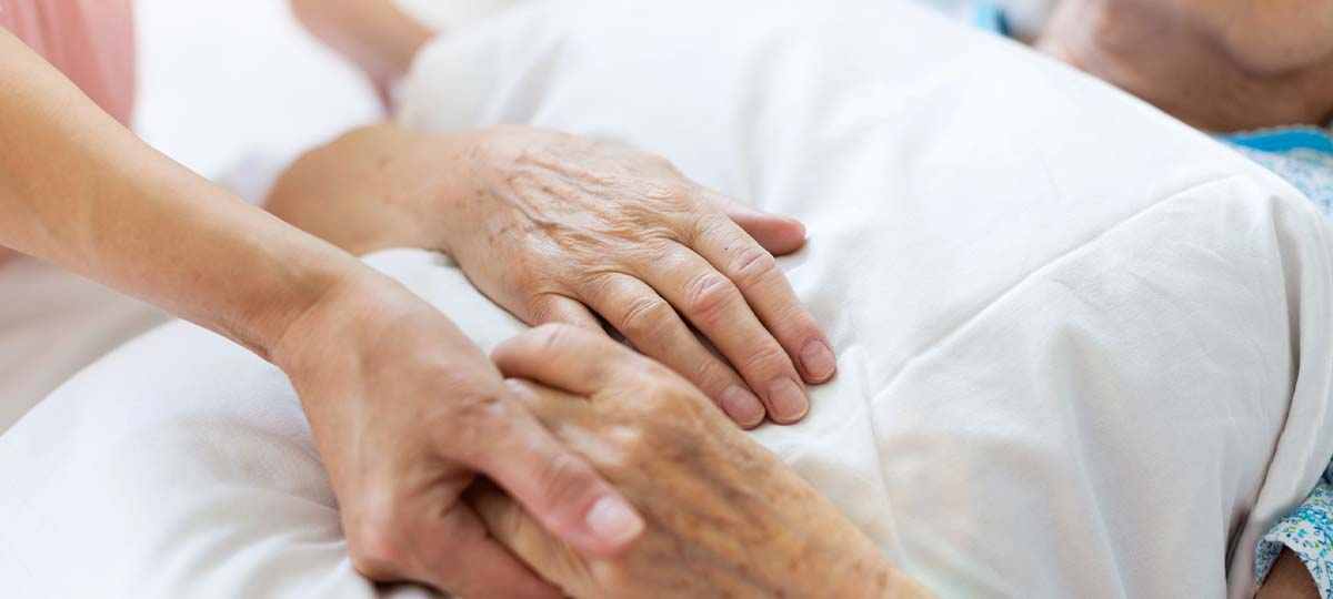 Young hand holding older hands of patient laying down in hospital bed