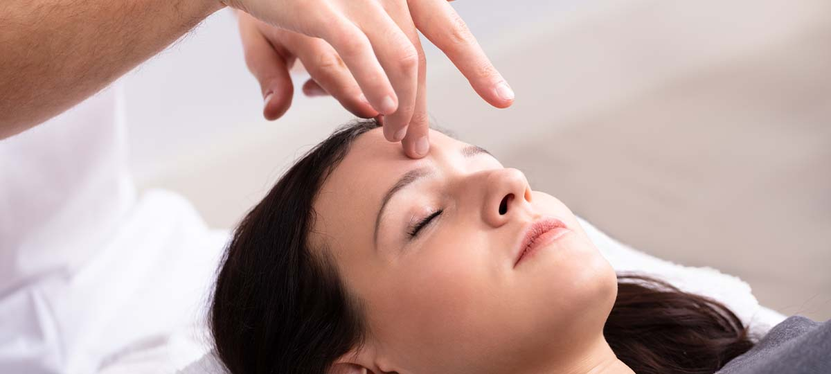 Person laying down with eyes closed therapists fingertip on forehead