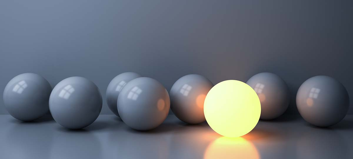 Eight gray marbles on a table with one bright and illuminated