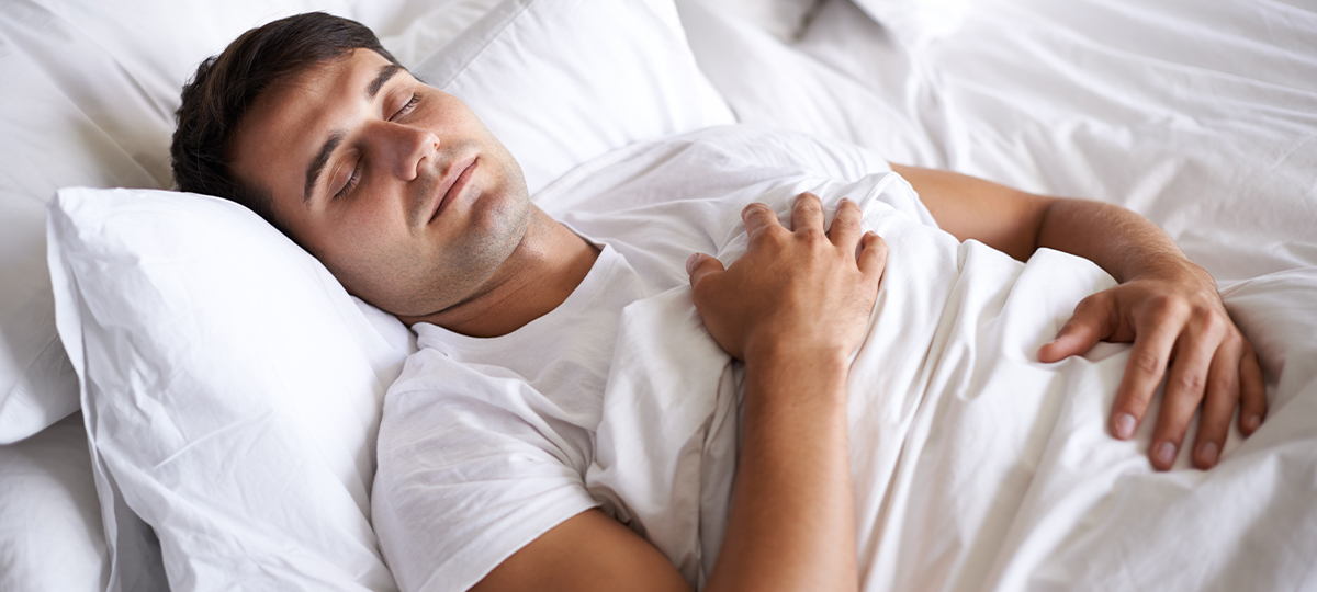 Person lying in bed hands on chest asleep