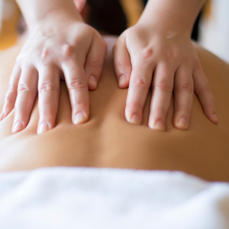 massage therapist's hands massaging client's back